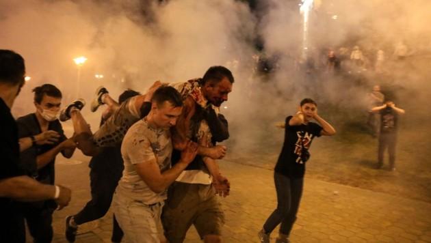 Ein verwundeter Mann wird von Demonstranten weggetragen. (Bild: AP)
