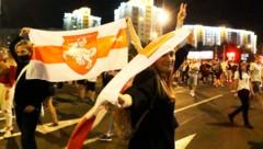 Demonstrantinnen mit der weißrussischen Flagge (Bild: AP)