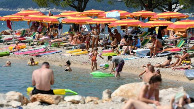 Sonnenschirm an Sonnenschirm an diesem Adria-Strand in Crikvenica - ab Mitternacht von Sonntag auf Montag gilt für Kroatien eine Reisewarnung.