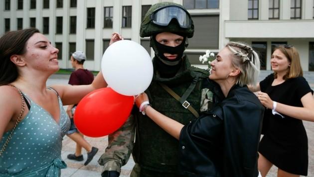 Aus Solidarität mit den Menschen senkten Soldaten am Regierungssitz ihre Schilde, Frauen schenkten ihnen Blumen. (Bild: AP)