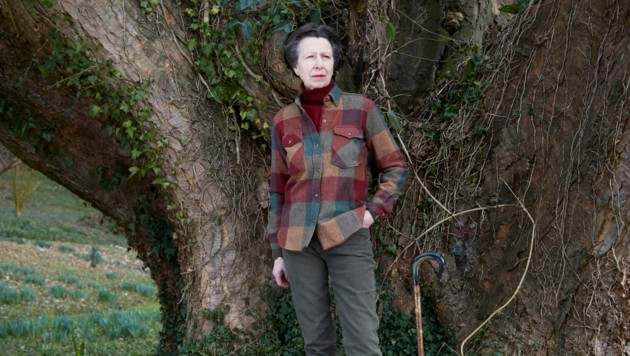 Ein Foto zeigt Prinzessin Anne naturverbunden vor einem großen Baum mit karierter Bluse und Spazierstock. (Bild: AFP)