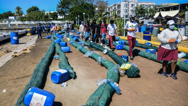 Freiwillige helfen beim Zusammenbauen von Öl-Barrieren, die das ausgelaufene Öl absorbieren sollen. (Bild: AFP)