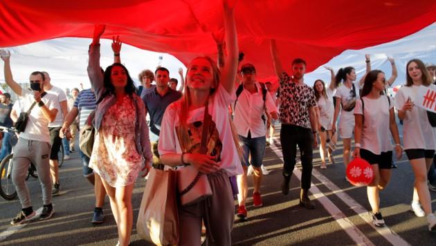 Lukaschenkos Gegner demonstrierten unter einer veralteten weißrussischen Flagge. (Bild: AP)