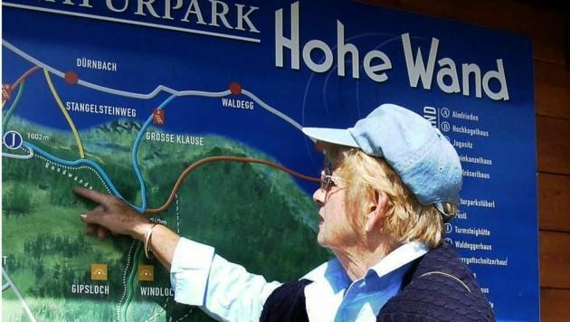Eine Pensionistin betrachtet die Wanderroute des Naturparkgebietes Hohe Wand.