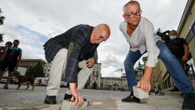 Gert Kerschbaumer (links) und Thomas Randisek verlegen zwei der Erinnerungssteine