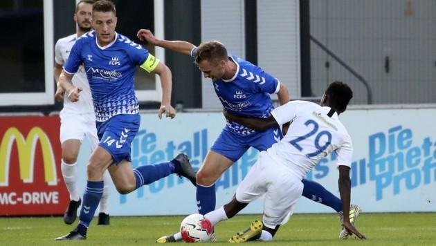 Trafen beim 2:0 in Grödig: Die FC Pinzgau-Spieler Tandari (Ii.) und Schubert (im blauen Dress) (Bild: Tröster Andreas)