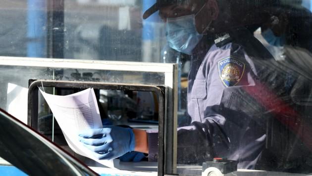 Ein kroatischer Polizeibeamter bei der Kontrolle Einreisender an der slowenisch-kroatischen Grenze in Bregana