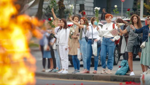 Unterstützer der weißrussischen Opposition halten in der Hauptstadt Minsk aus Protest Blumen in den Händen, um ihrem Wunsch nach einem Rücktritt von Präsident Lukaschenko Ausdruck zu verleihen. (Bild: AP)