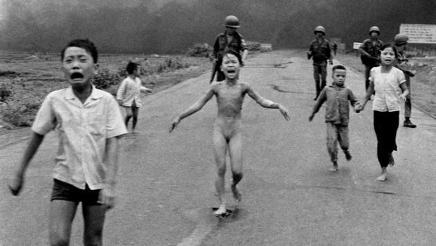 Nackt und schreiend vor Schmerzen läuft die damals neunjährige Kim nach dem Brandbombenangriff mit ihren Brüdern und Cousins über eine Straße, im Hintergrund dicker Qualm.