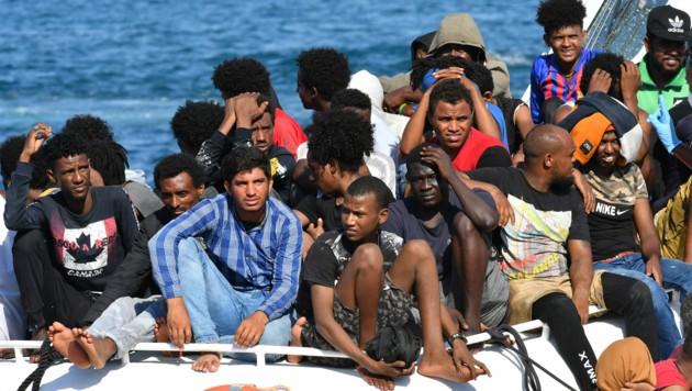 Migranten aus Tunesien und Libyen bei der Ankunft auf Lampedusa (Bild: AFP)