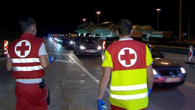 Mitarbeiter des Roten Kreuzes betreuten Autoinsassen in dem kilometerlangen Stau bei der Einreise am Karawankentunnel. (Bild: APA/ORF Kärnten)