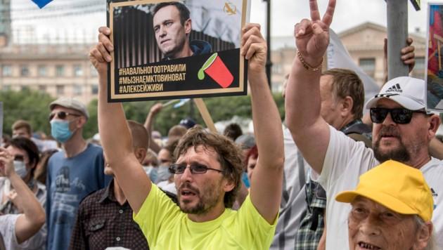 """Ein Demonstrant hält ein Schild von Kreml-Kritiker Alexej Nawalny in die Höhe, auf dem steht: """"Nawalny wurde vergiftet. Wir wissen, wer Schuld hat. Alexej, du musst leben."""""""