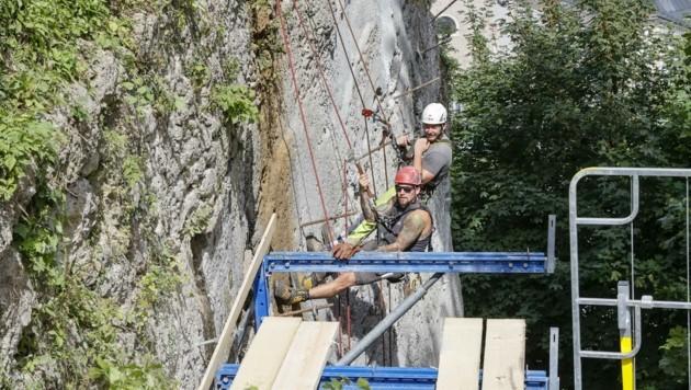 In luftigen Höhen baumeln die Bauleute bei der Restaurierung am Mönchsberg.
