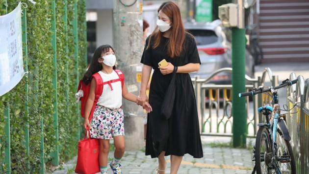 Mutter und Tochter vor einer Schule in Südkorea (Archivbild) (Bild: AFP)