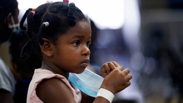 Skyler Lawson (4) wartet darauf, mit ihren Eltern in Sichrheit gebracht zu werden. (Bild: AP Photo/Gerald Herbert)