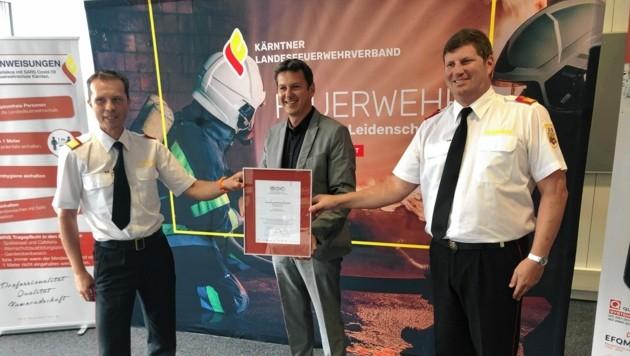 Landesrat Daniel Fellner, Landesfeuerwehrchef Rudolf Robin und Klaus Tschabuschnig, Leiter der Landesfeuerwehrschule, mit dem Qualitätssiegel Ö-Cert.