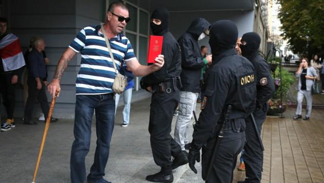 Ein Demonstrant hält einem weißrussischen Polizisten eine Kopie des Strafgesetzbuches ins Gesicht. (Bild: AP)
