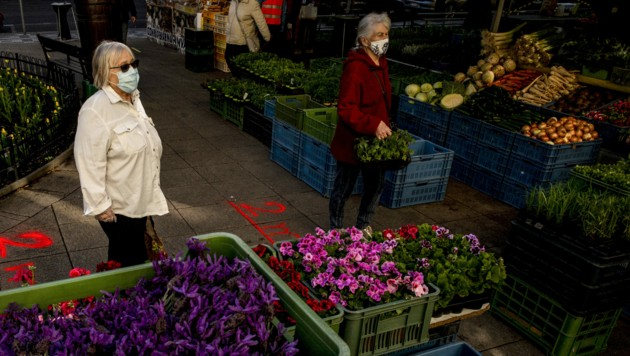 Women wearing face masks walk at the reopened farmer market as marks indicating 2m distance are sprayed on the floor on April 20, 2020 in Prague. - Some restrictions imposed to help combat the spread of Covid-19 were lifted in the Czech Republic on Monday. (Photo by Michal Cizek / AFP) (Bild: AFP )