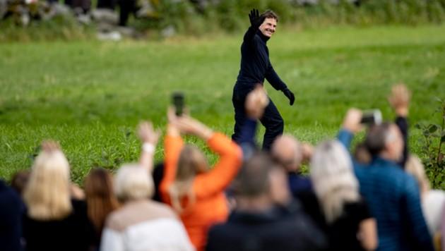 Tom Cruise nahm sich nach dem Mega-Stunt kurz Zeit für die Zaungäste, die das Spektakel beobachtet hatten. (Bild: AFP)