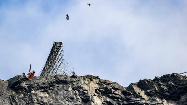 Tom Cruise raste mit dem Motorrad über eine Rampe auf den 1249 Meter tiefen Abgrund zu. (Bild: Geir Olsen / NTB scanpix / picturedesk.com)