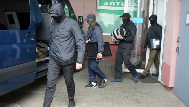 Weißrussische Einsatzkräfte bringen beschlagnahmtes Material aus einer Wohnung (Bild: AP)