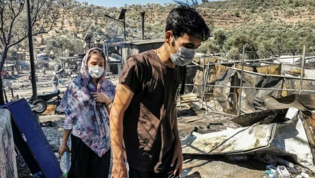Nach dem verheerenden Feuer im Flüchtllingscamp suchen Betroffene nach ihren Habseligkeiten.