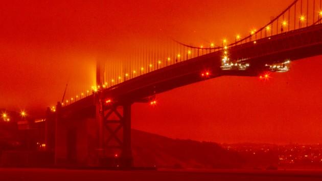 Die weltberühmte Golden Gate Bridge ist von einem dichten orangefarbenen Rauch umhüllt. (Bild: AP)