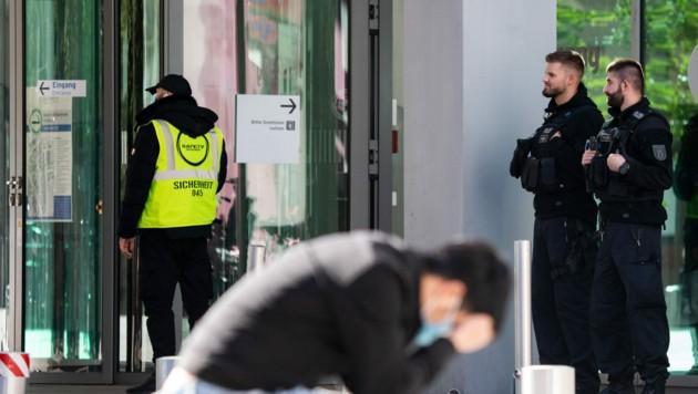Polizisten und ein Sicherheitsmitarbeiter stehen vor dem Haupteingang der Berliner Charité. Um ein neuerliches Attentat auf den Kreml-Kritiker zu verhindern, sind die Sicherheitsmaßnahmen zuletzt weiter verstärkt worden. (Bild: APA/dpa/Bernd von Jutrczenka)