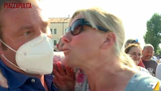 Cunial umarmt den perplexen Journalisten und versucht, ihn auf die Wange zu küssen. (Bild: Twitter.com/PiazzapulitaLA7)