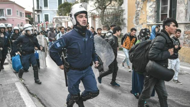 Polizisten bringen Flüchtlinge im März 2020 zurück ins Camp Moria. (Bild: LOUISA GOULIAMAKI/AFP)