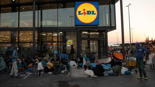 Migranten campieren vor einer Lidl-Filiale auf der griechischen Insel Lesbos. (Bild: AP)