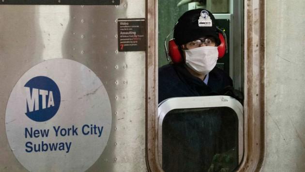 Ein Lokführer der New Yorker U-Bahn trägt einen Mund-Nasen-Schutz.