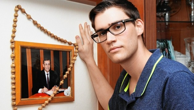 Reinhard Dill vor einem Bild seines verstorbenen Vaters