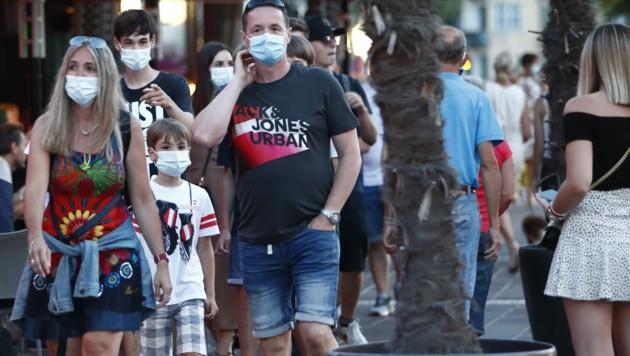 Bei einem Spaziergang durch Velden tragen diese Personen Masken. (Bild: APA/GERT EGGENBERGER)