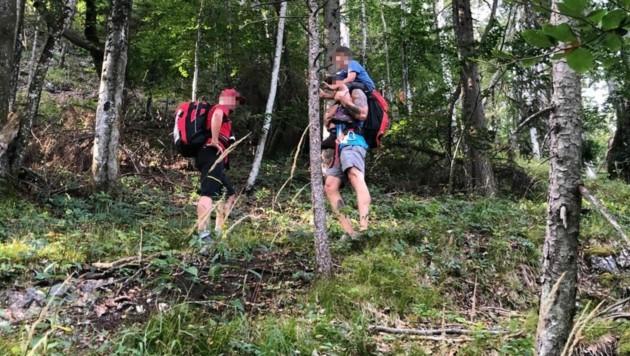 Ein Bergretter nahm den stark erschöpften Buben auf seine Schultern und trug ihn ins Tal. (Bild: Bergrettung Bad Ischl)