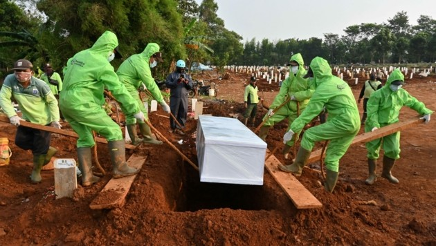Särge von Covid-19-Opfern werden in Indonesien ausschließlich in Schutzausrüstung beerdigt. (Bild: AFP)