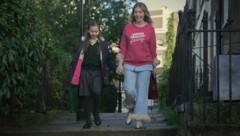 """""""Die Diva"""": Katherine (gespielt von Katherine Ryan) bringt ihre Tochter Olive (Kate Byrne) im Edelpyjama in die Schule. (Bild: © 2020 Netflix, Inc.)"""