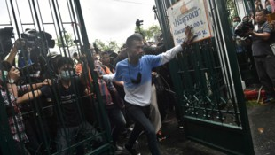 Die demonstrierenden Studenten in Thailand durchbrachen die Tore der abgesperrten Thammasat-Universität, um gegen die Regierung zu demonstrieren. (Bild: AFP)