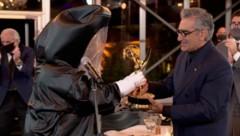 """Schauspieler Eugene Levy bekommt seinen Emmy als bester Hauptdarsteller in der Comedy-Serie """"Schitt's Creek"""" von einer Person in einem Corona-Schutzanzug überreicht. (Bild: APA/AFP PHOTO / Image Group LA / American Broadcasting Companies, Inc. / ABC)"""