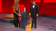 """Jennifer Aniston war einer der wenigen Stars, die die Emmy-Preisverleihung 2020 nicht von einem sicheren Ort aus verfolgten, sondern zu Moderator Jimmy Kimmel ins Staples-Center kamen. Als Gag """"desinfizierten"""" die beiden den Umschlag mit der besten Comedy-Hauptdarstellerin mit Feuer. (Bild: APA/The Television Academy and ABC Entertainment via AP)"""