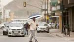 Mit einen Schirm schützt sich dieser Mann vor dem Ascheregen. (Bild: AP)