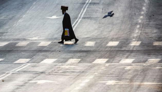 Ein ultra-orthodoxer Jude geht über eine wegen des Lockdowns verlassene Straße in Bnei Brak. (Bild: AP)