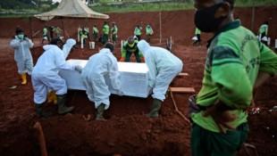 Auf einem Friedhof vor den Toren von Jakarta (Indonesien) heben Totengräber fast ununterbrochen neue Gräber für Coronavirus-Tote aus. (Bild: The Associated Press)