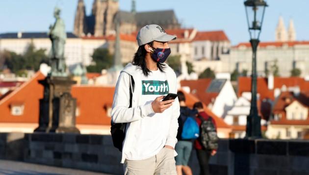 Ein Passant mit Maske auf der Karlsbrücke in Prag (Bild: AP)