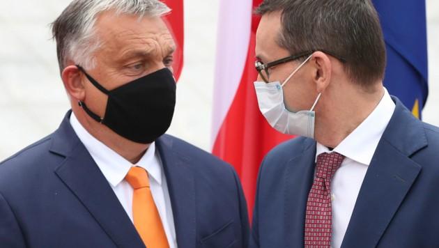 Polens Ministerpräsident Mateusz Morawiecki und sein ungarischer Amtskollegen Viktor Orban (li.) proben den Aufstand. (Bild: The Associated Press)