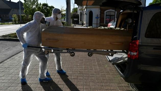 Die Mitarbeiter eines Bestattungsunternehmens außerhalb des Saint-Luc Krankenhauses in der belgischen Stadt Namur. (Bild: AFP)