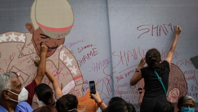 """Die Karikatur eines Polizisten wird während eines Protests wegen der verschleppten Ermittlungen mit """"Schande"""" beschmiert. (Bild: AP)"""