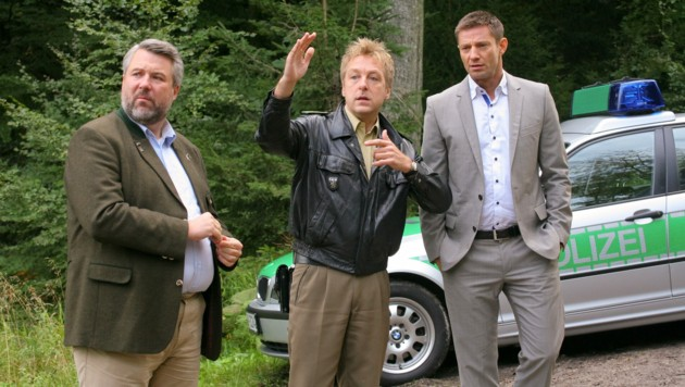 """""""Die Rosenheim-Cops: Tod am Schlagbaum"""": Kommissar Stadler (Dieter Fischer), Polizist Mohr (Max Müller) und Kommissar Hansen (Igor Jeftic) vor einem Polizeiauto im Wald stehend, ermitteln in einem Mordfall. (Bild: ZDF/Christian A. Rieger)"""