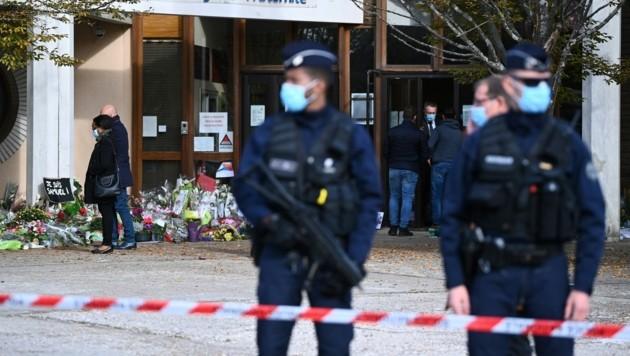 Immer mehr Blumen, Transparente und Kerzen werden für den getöteten Lehrer vor seiner Schule abgelegt. (Bild: APA/AFP/Anne-Christine POUJOULAT)