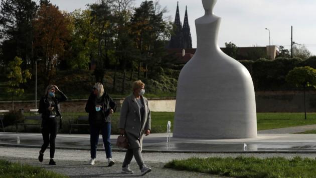 Auch im Freien müssen in Tschechien noch immer Masken getragen werden, wie hier in Prag. (Bild: AP)
